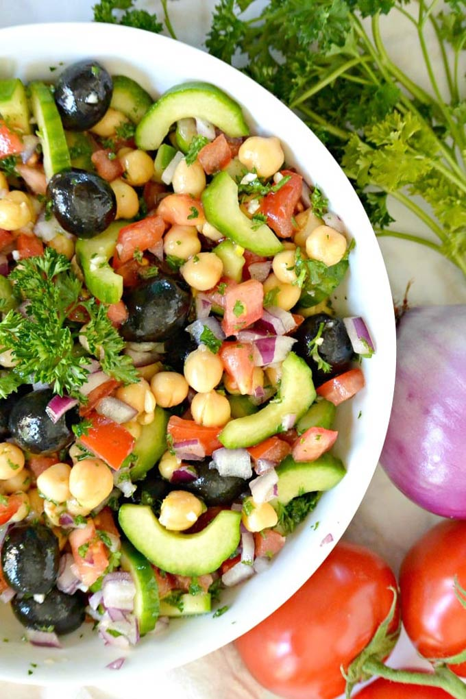 Chickpea cucumber salad with tomatoes and olives in a white bowl, surrounded by fresh veggies.