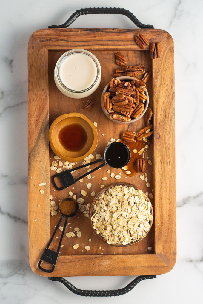 Ingredients for maple pecan overnight oats: dairy-free milk, pecans, vanilla, maple syrup, cinnamon and oats.