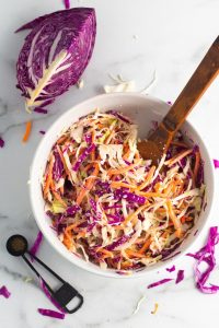 Easy vegan coleslaw in a white bowl with red cabbage, green cabbage, and carrots.