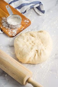 A ball of pizza dough on a flour surface with a rolling pin.
