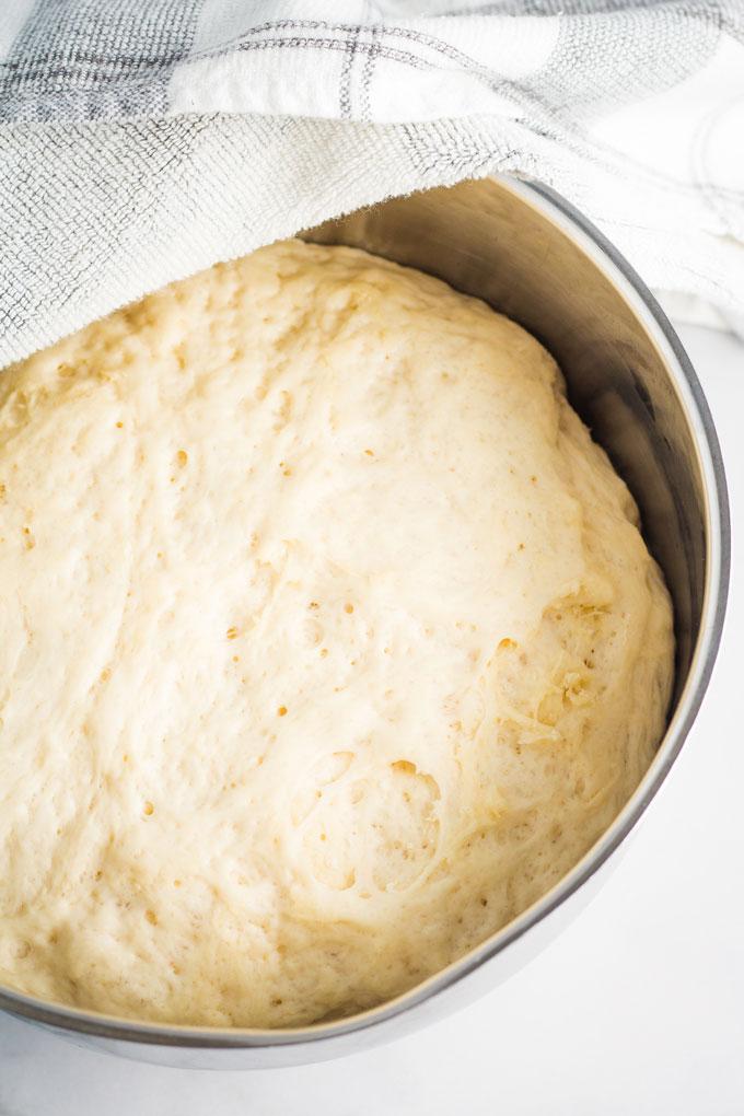 Pizza dough rising a silver-colored bowl.