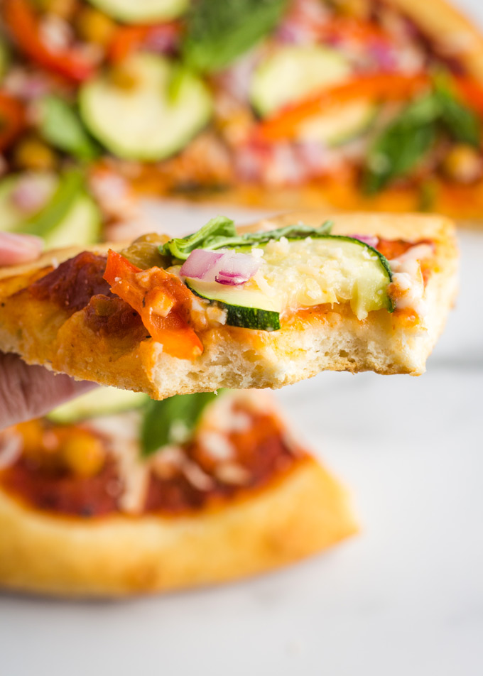 A slice of vegan pizza topped with bell peppers, zucchini, vegan cheese, chickpeas and basil being held up with a bite taken out.