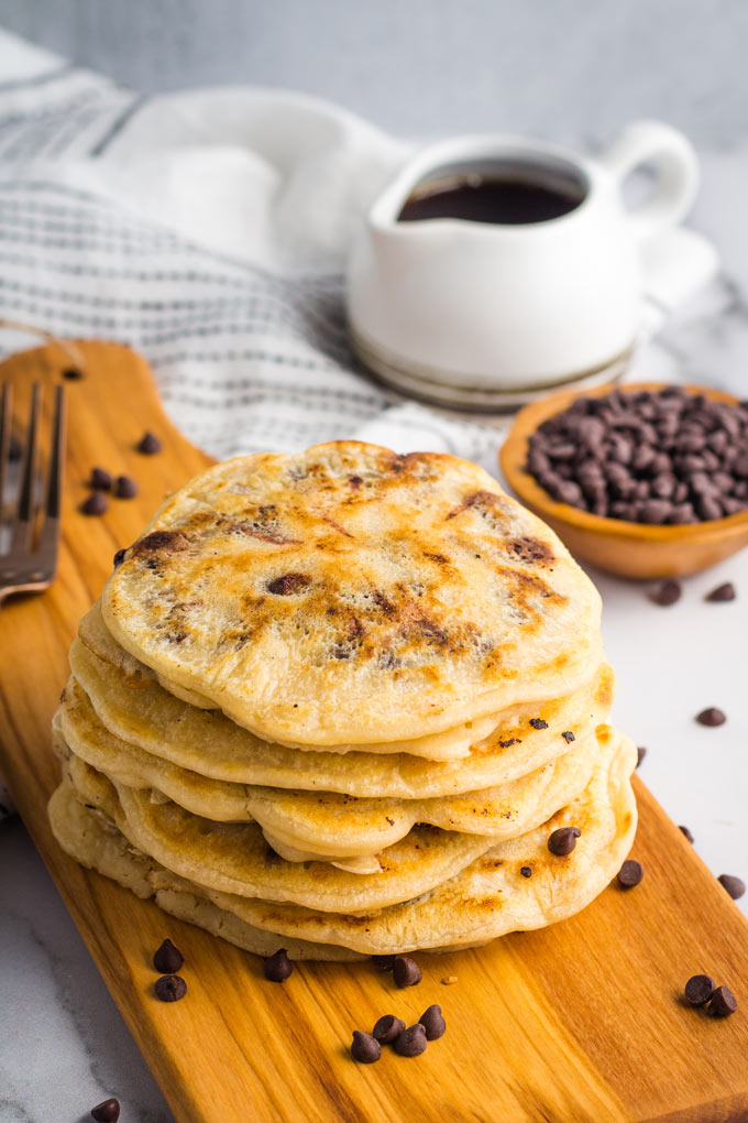 A stack of chocolate chip pancakes on a wooden board, with a bowl of chocolate chips and maple syrup in the background.