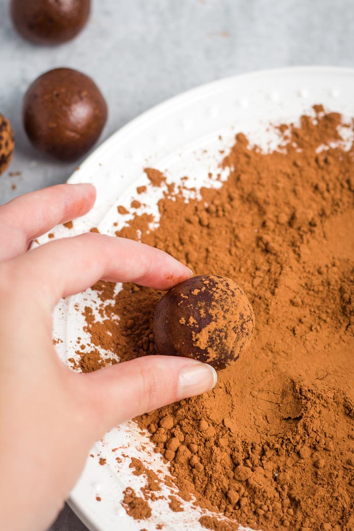 A chocolate peanut butter protein ball being rolled into cocoa powder.