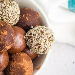 Chocolate peanut butter protein balls piled into a bowl. Some are plain, some coated in hemp seeds, some coated in cocoa powder.