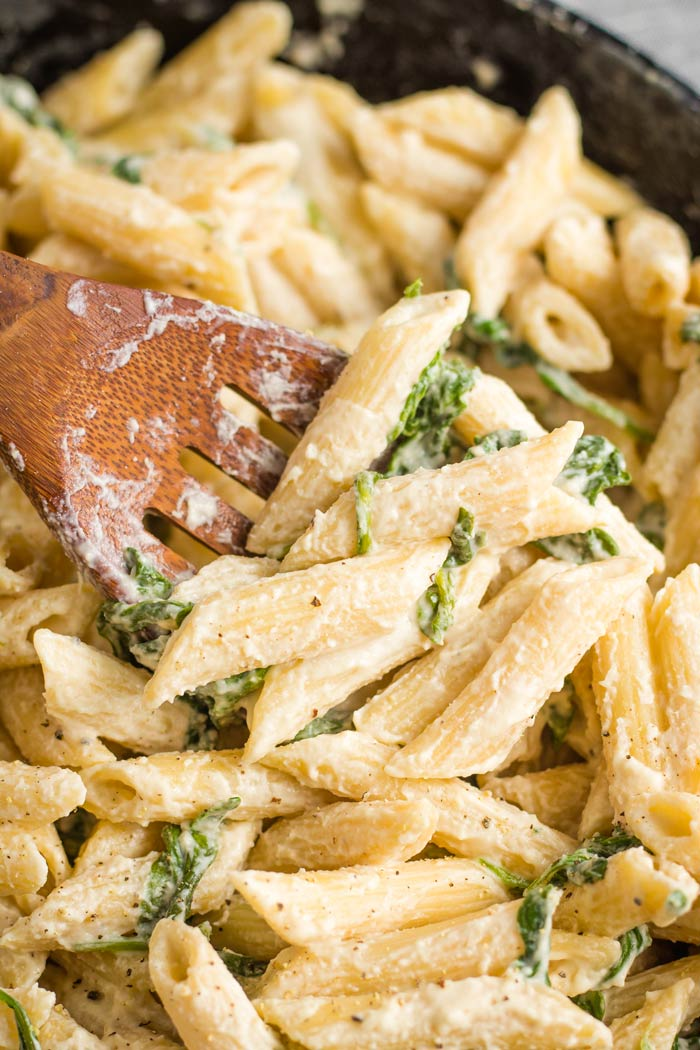 Close-up of One-Pot Creamy Spinach Pasta on a wooden spoon