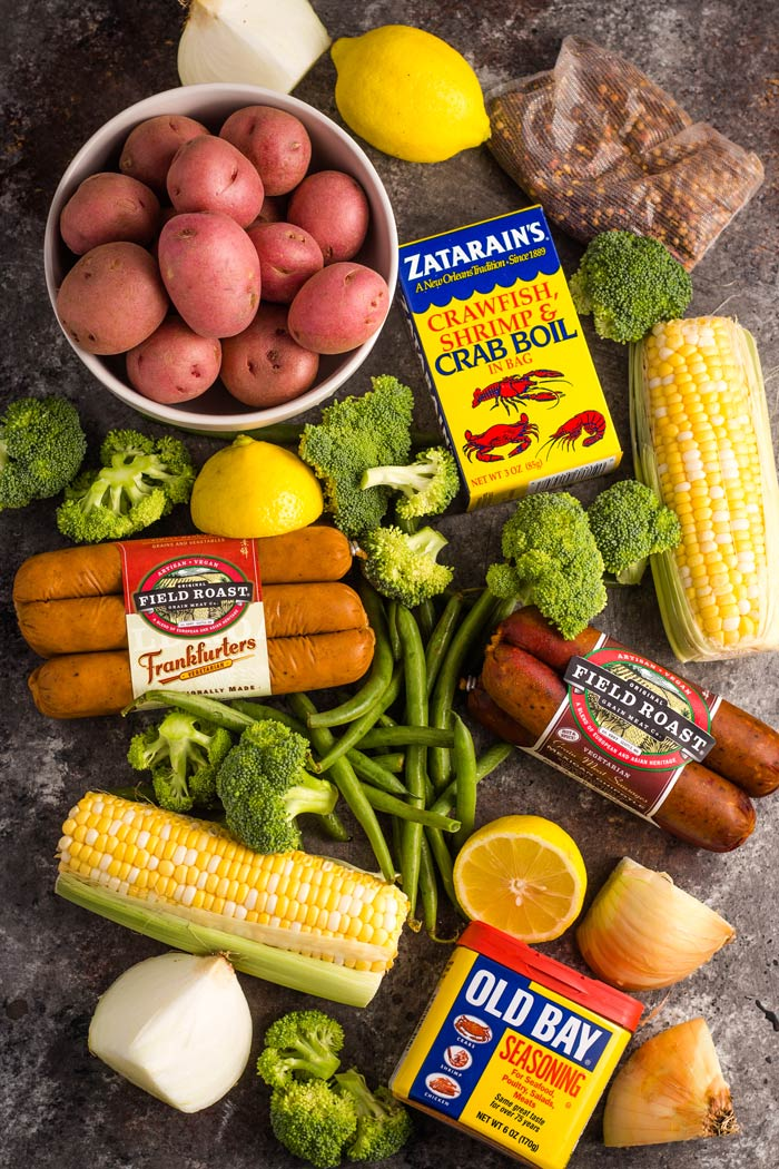 Ingredients for a vegan boil laid out on a surface - red potatoes, corn on the cob, broccoli florets, green beans, vegan sausage, and seasoning.