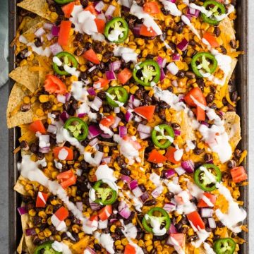 Vegan sheet pan nachos topped with cheese, beans, sour cream, corn, jalapenos, tomatoes and red onions.