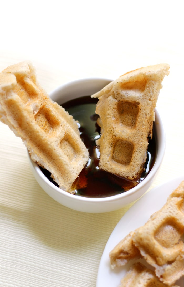 Freezable vegan waffles dipped in maple syrup.