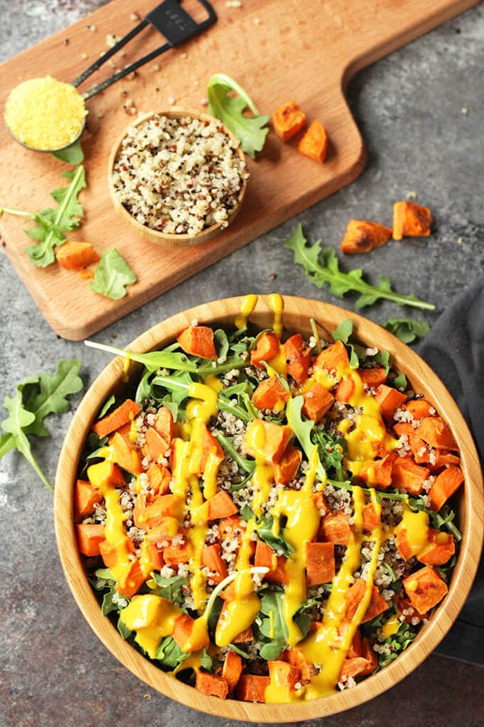 Sweet potatoes, quinoa, and sweet mustard dressing over a bed of arugula