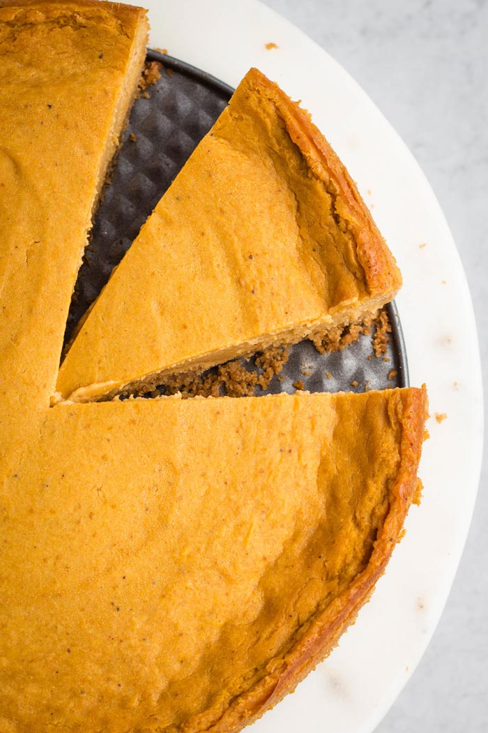 A close-up of dairy-free pumpkin cheesecake with a slice taken out.