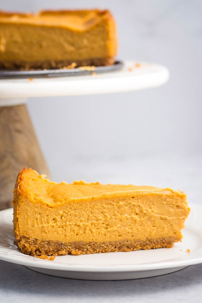 A slice of vegan pumpkin cheesecake on a white plate.