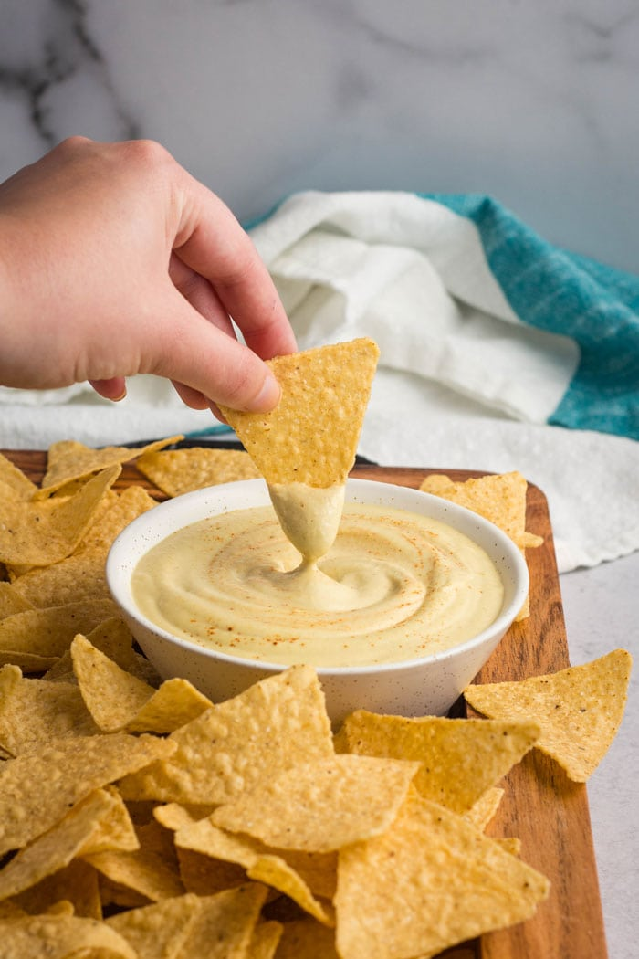 A tortilla chip being dipped into white vegan queso.