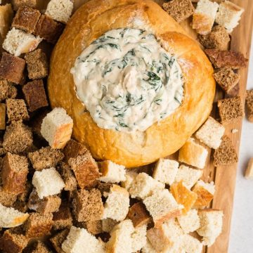 Vegan spinach dip in a bread bowl surrounded by bread cubes for dipping.