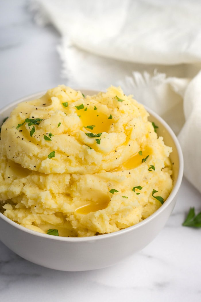 A close-up of mashed potatoes topped with butter and parsley.