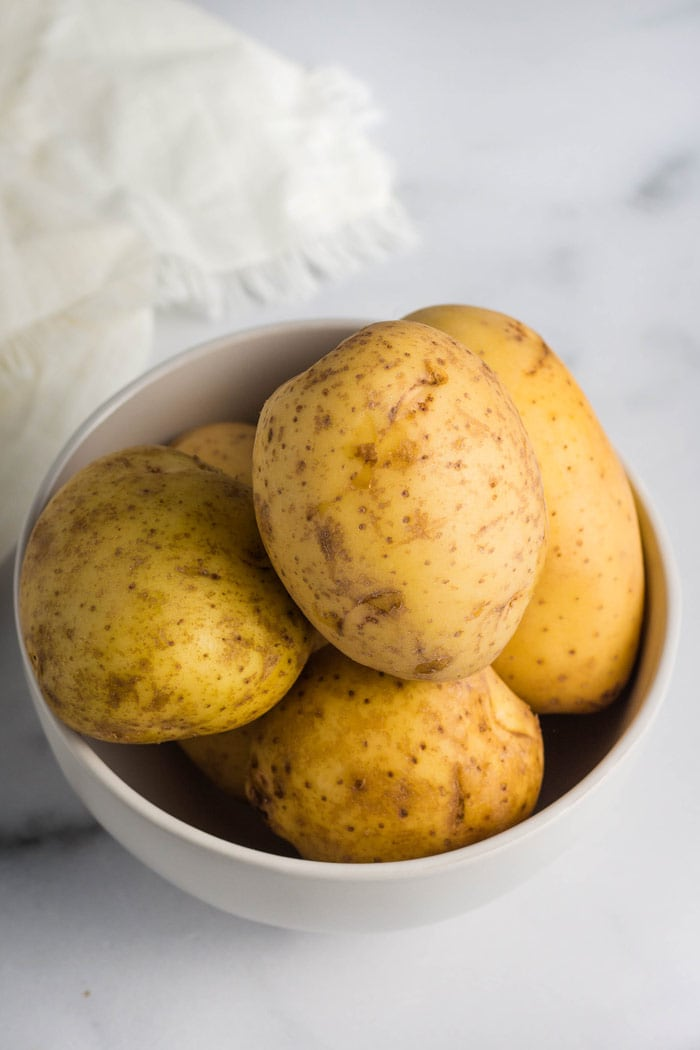 Gold potatoes in a bowl ready to be peeled for mashed potatoes.