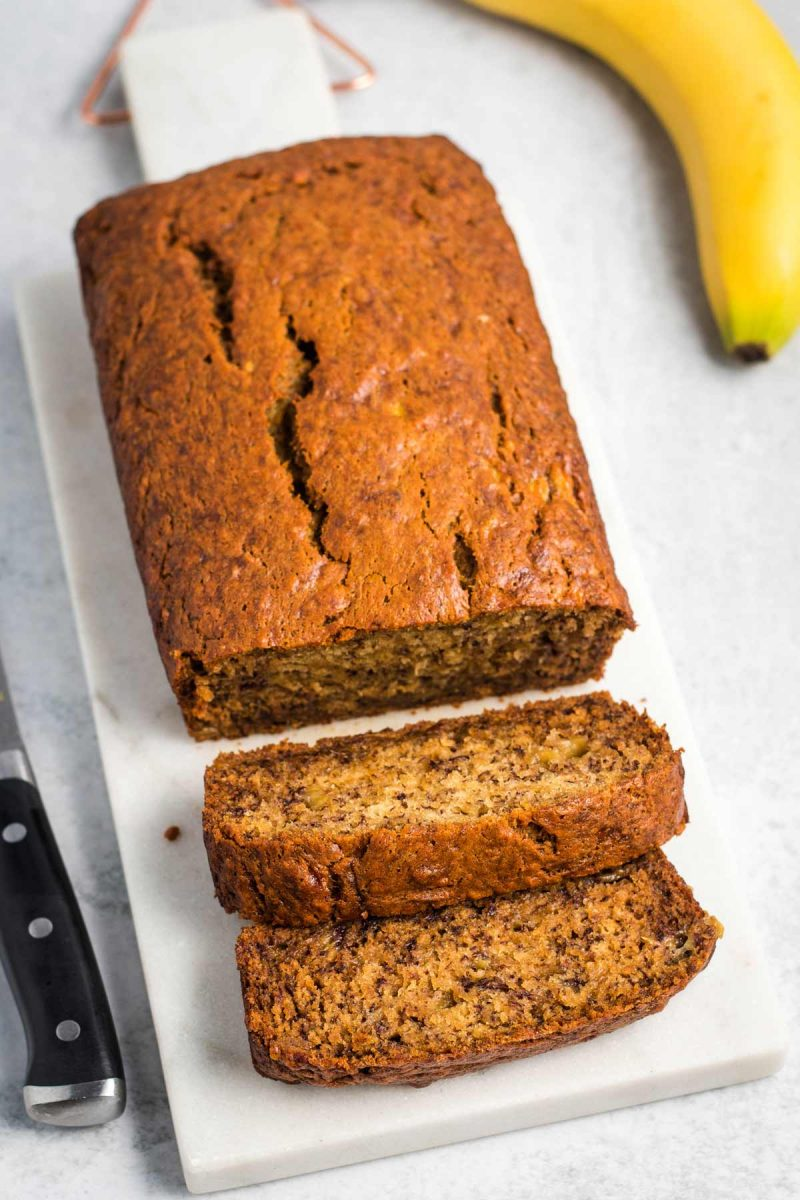 A loaf of baked vegan banana bread with 2 slices cut.