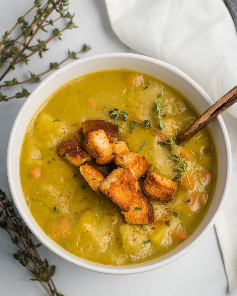 Vegan split pea soup in a white bowl topped with croutons.