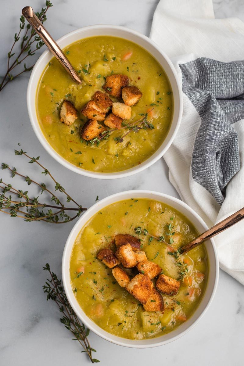 Two white bowls full of split pea soup, garnished with thyme and croutons, with gold spoons.