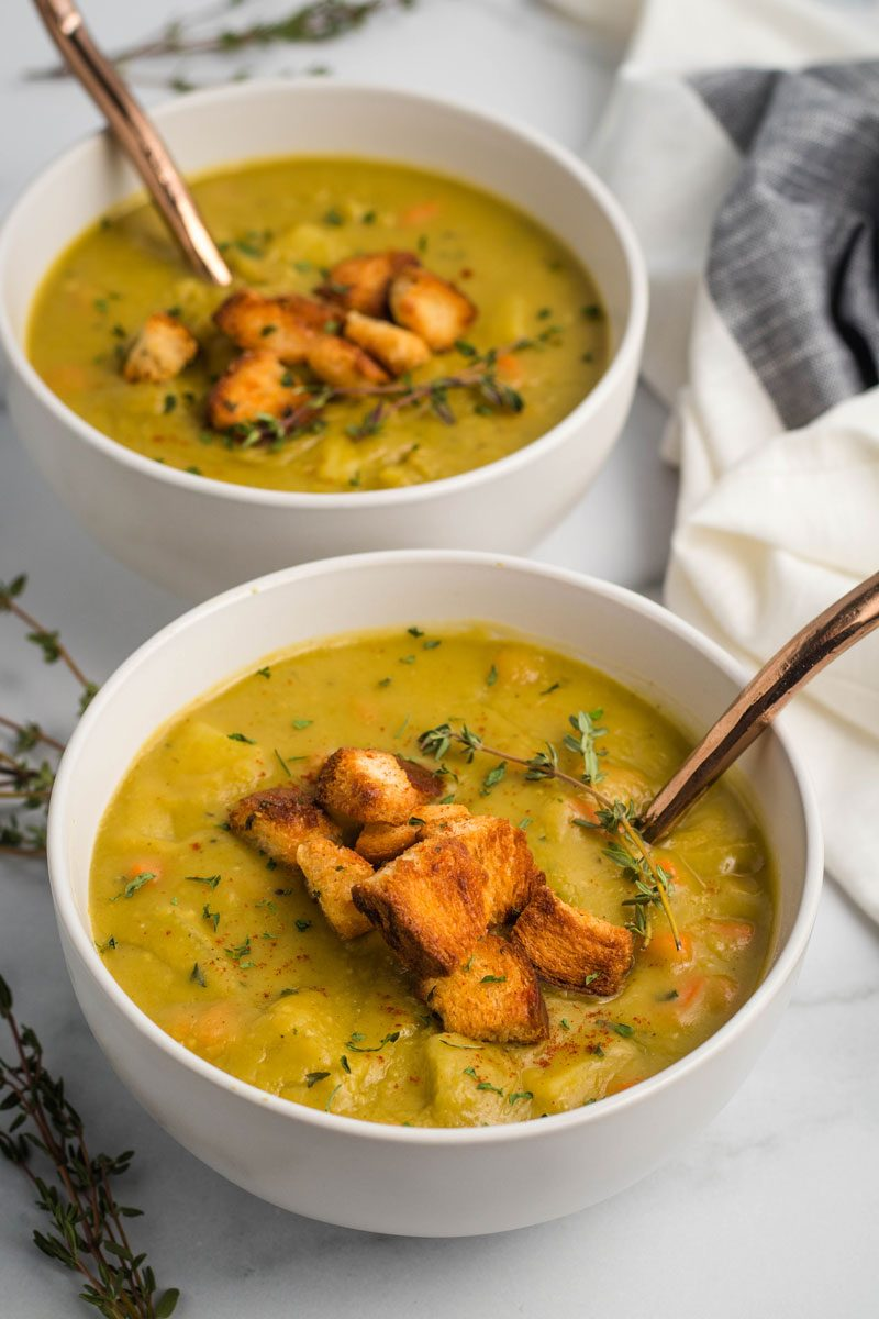 Two bowls of vegetarian split pea soup topped with thyme and croutons.