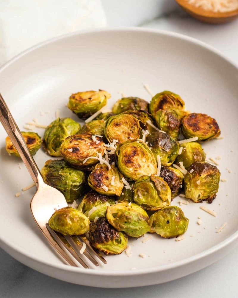 Vegan roasted Brussels sprouts in a bowl with a fork, sprinkled with parmesan.