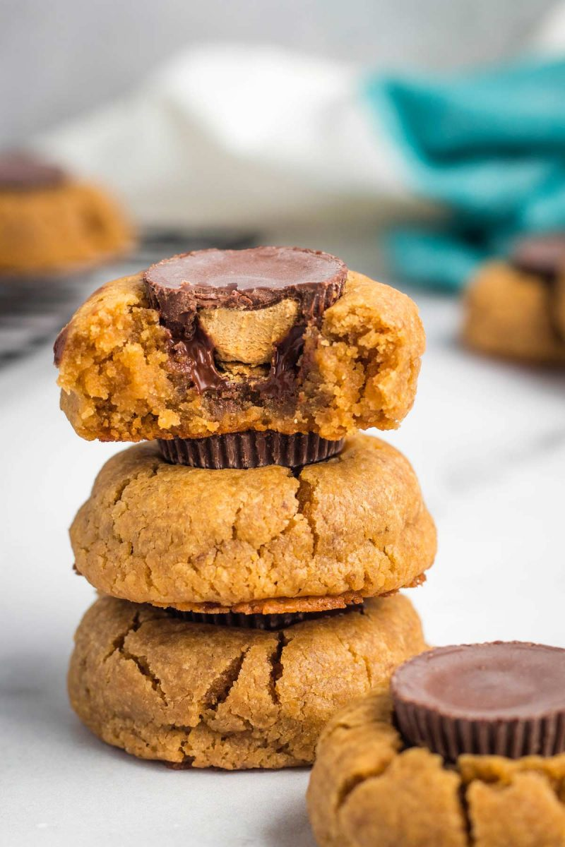 A stack of three peanut butter cup cookies, with a bite taken off the top one.