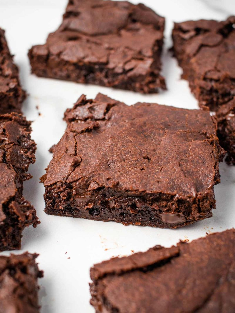 Baked brownies laid flat on a white surface.