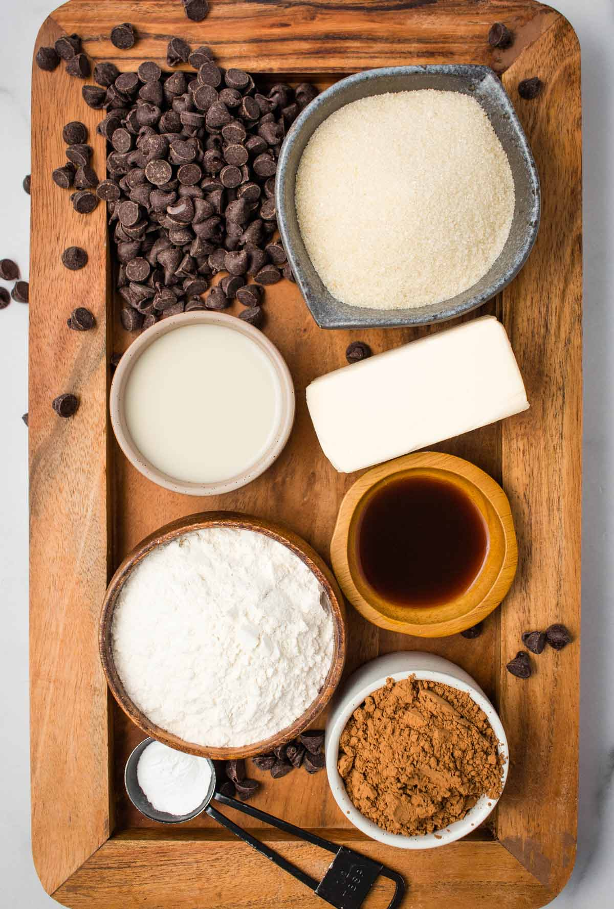 Ingredients on a wooden tray: non-dairy butter, sugar, cocoa powder, flour, vegan chocolate chips, vanilla extract, baking powder and salt.