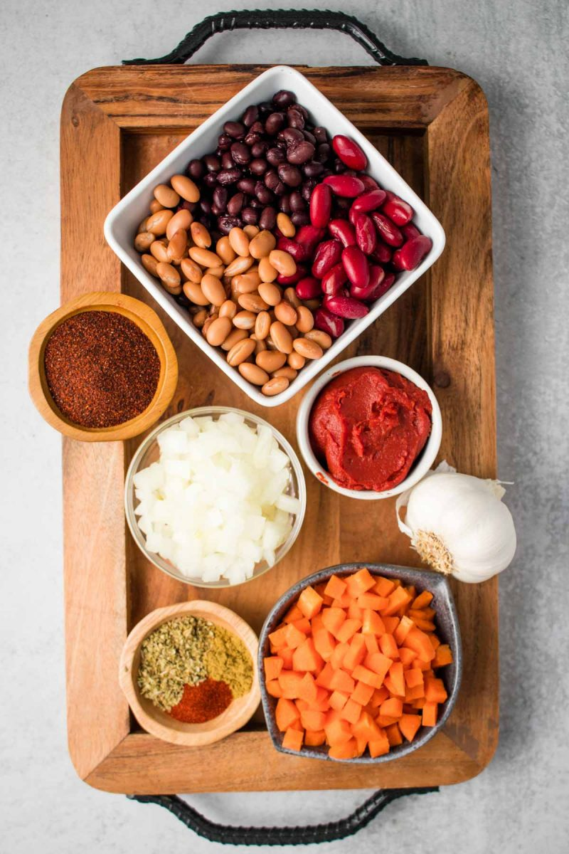 A wooden tray with vegan chili ingredients on it: beans, tomato paste, chili powder, oregano, cumin, smoked paprika, paprika, carrots, garlic, and onions.