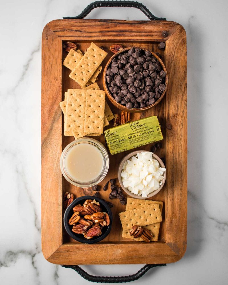 A tray with ingredients for 7 layer bars, aka magic cookie bars, on top: graham crackers, butter, chocolate chips, sweetened condensed coconut milk, coconut chips, and pecans.