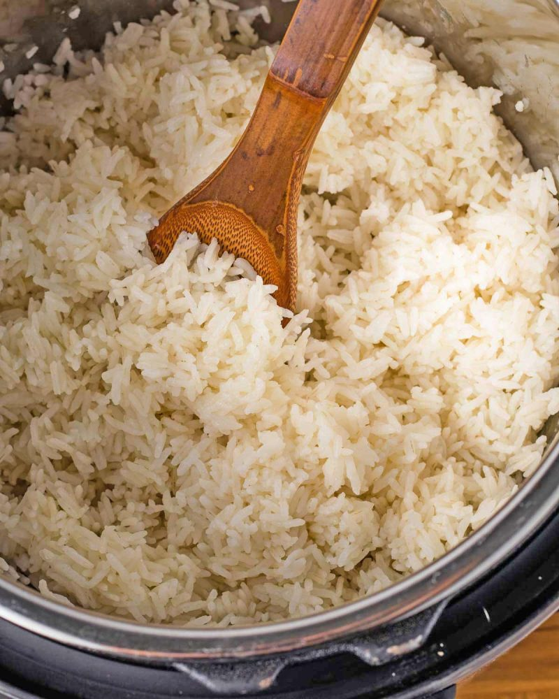 Cooked rice in the instant pot with a wooden spoon.