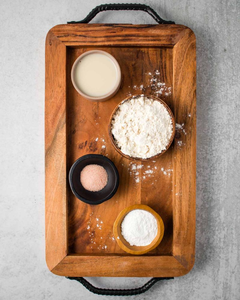 A wooden board with no-yeast bread ingredients on it: flour, dairy-free milk, salt and baking powder.