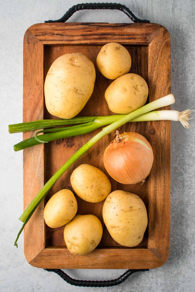 Gold potatoes, an onion, and green onions on a wooden board.