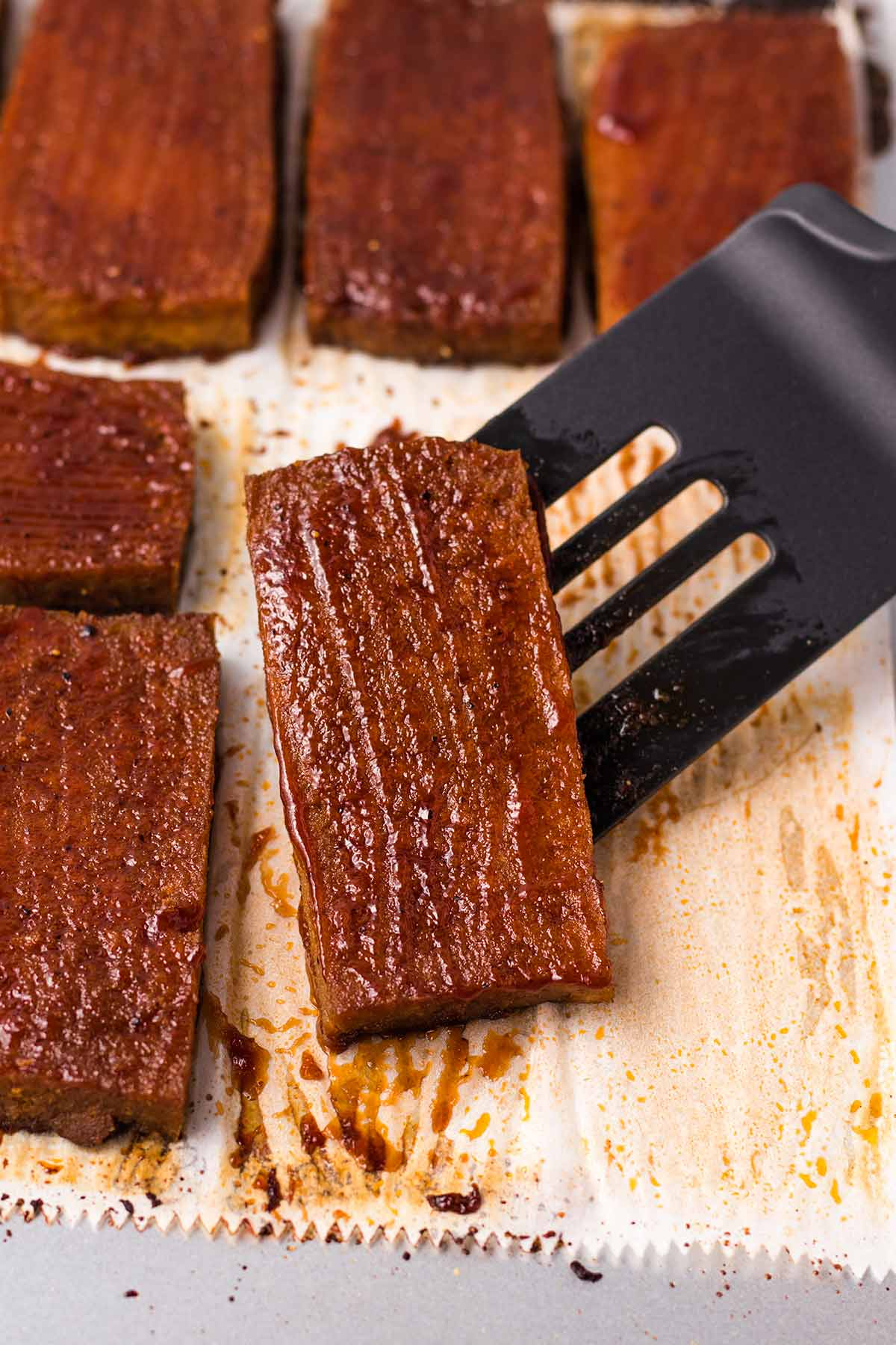 A spatula holding a slice of baked BBQ tofu on top of a sheet pan.