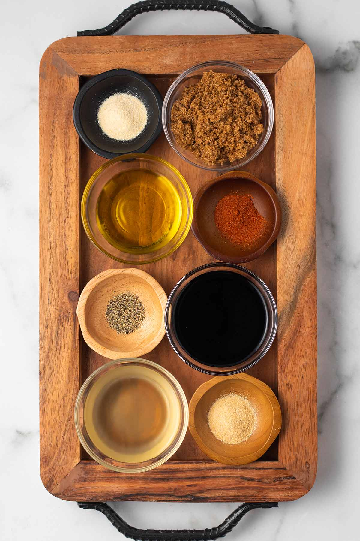 A wooden board with the ingredients for baked BBQ tofu marinade in small bowls. From left to right: onion powder, brown sugar, olive oil, smoked paprika, black pepper, soy sauce, apple cider vinegar, and garlic powder.