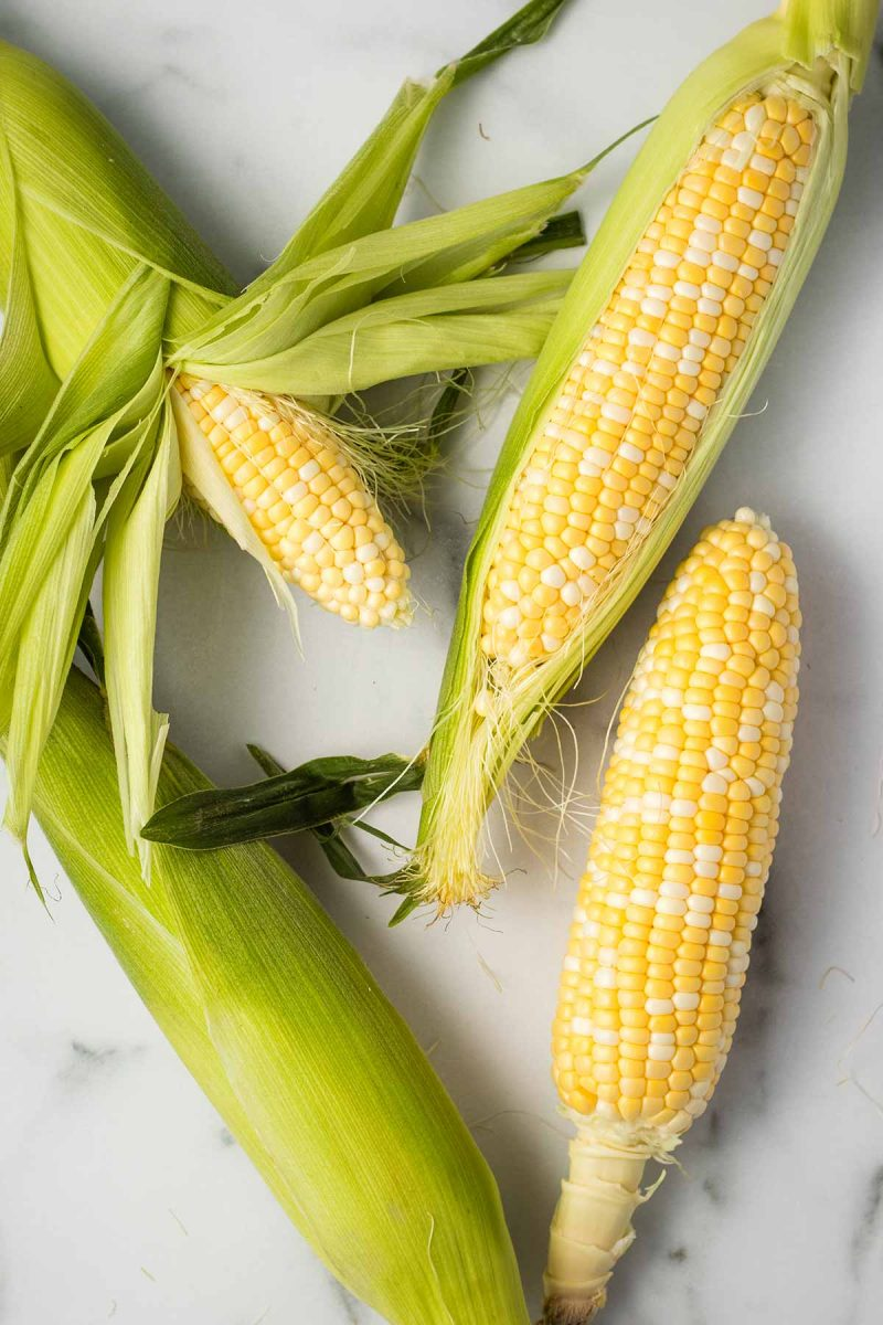 4 ears of corn on the cob laying flat in different directions. Two are partially shucked, one is fully shucked, and one still has the husk.