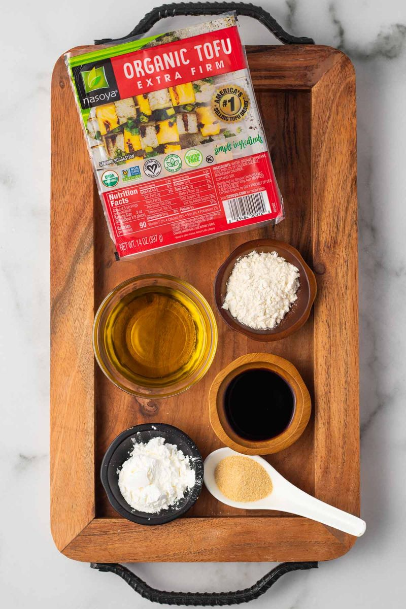 Ingredients for crispy tofu laid out on a wooden tray in small bowls: oil, flour, cornstarch, garlic, soy sauce, and extra firm tofu.