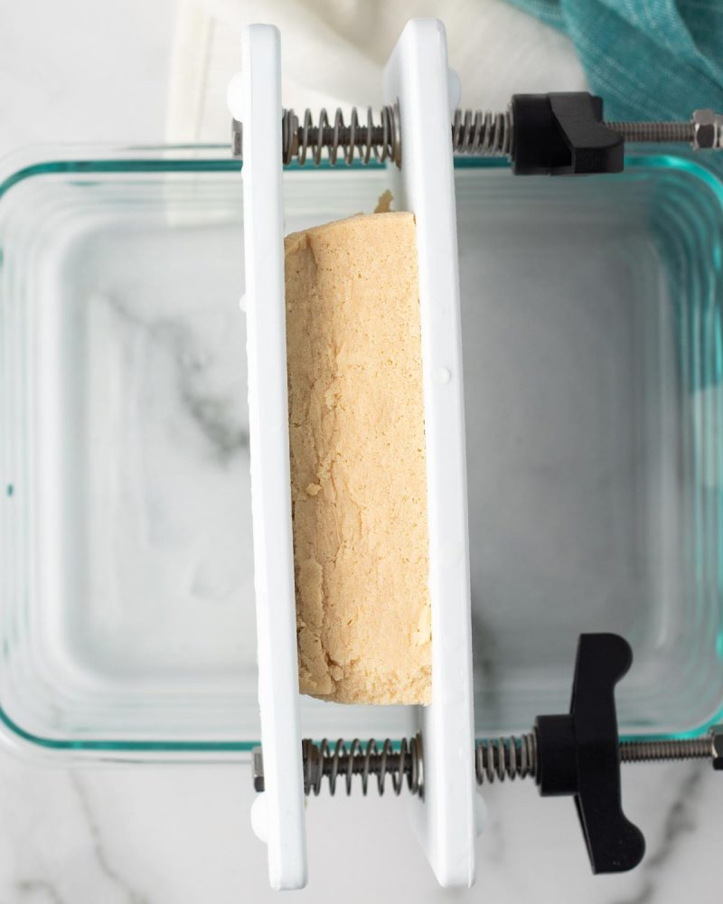 Tofu being pressed over a dish using a store-bought tofu press.