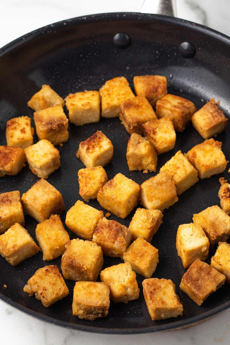 Crispy tofu cubes being fried in a large non-stick pan.