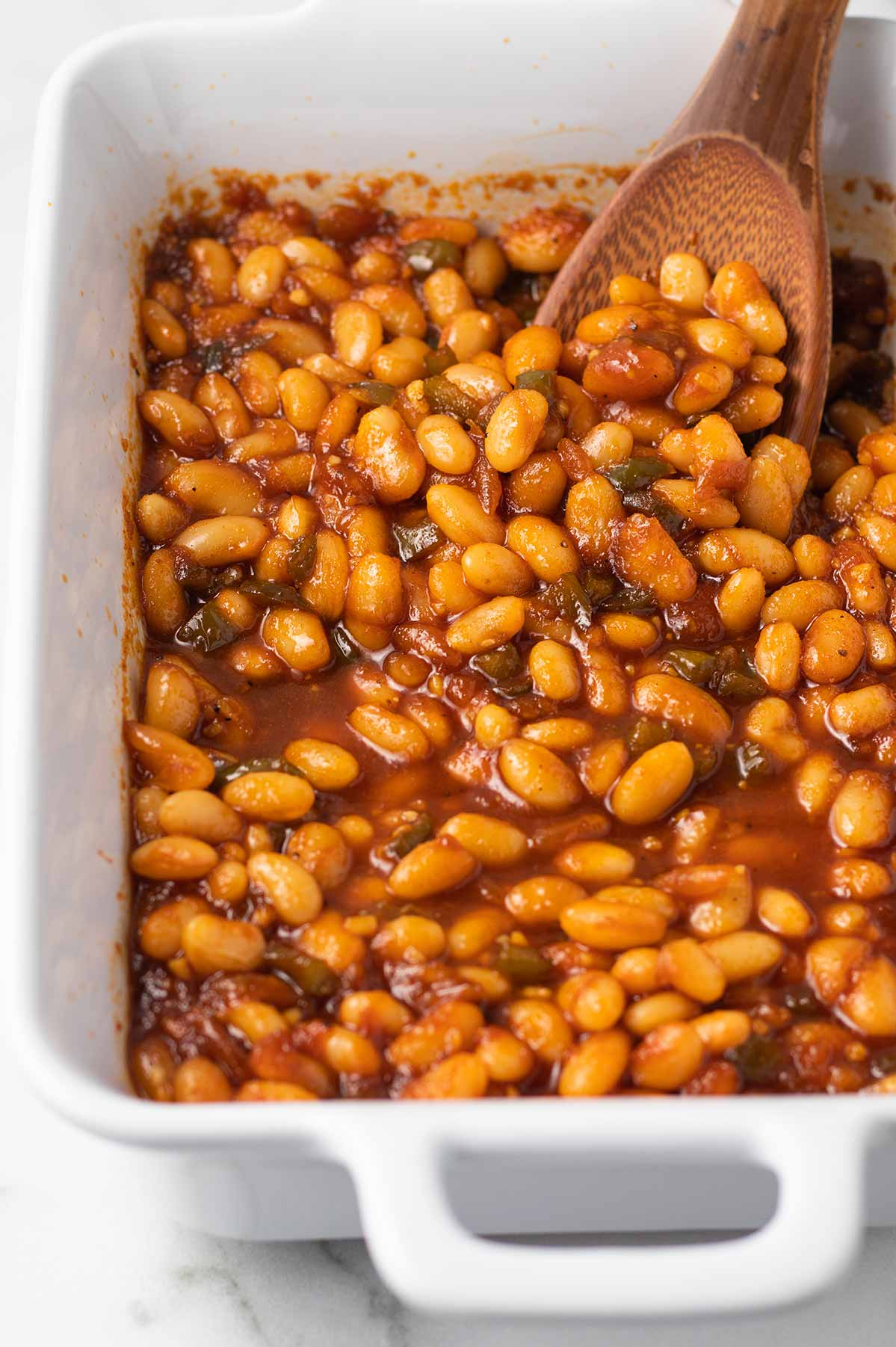 A close-up shot of vegan baked beans in a rectangle baking dish with a wooden spoon.