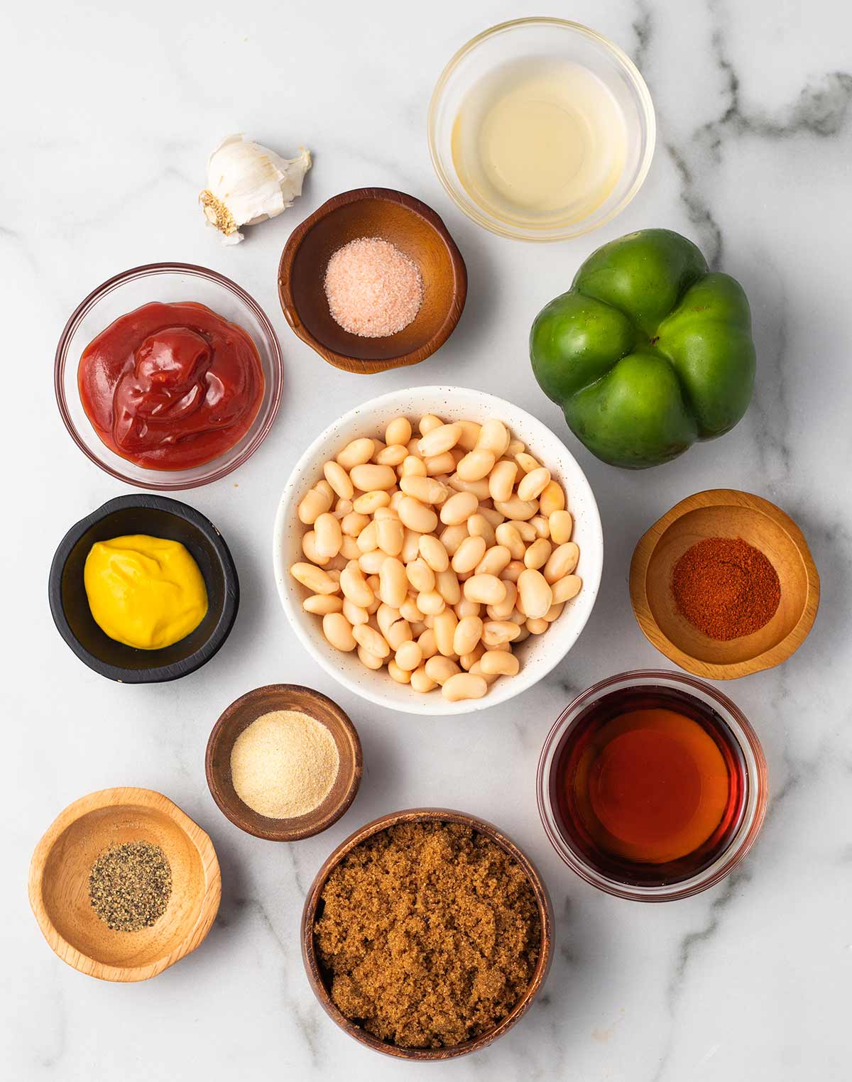 Ingredients for vegan baked beans laid in small bowls on a marble surface: beans, ketchup, green bell pepper, salt, apple cider vinegar, smoked paprika, maple syrup, brown sugar, garlic powder, pepper, and mustard.