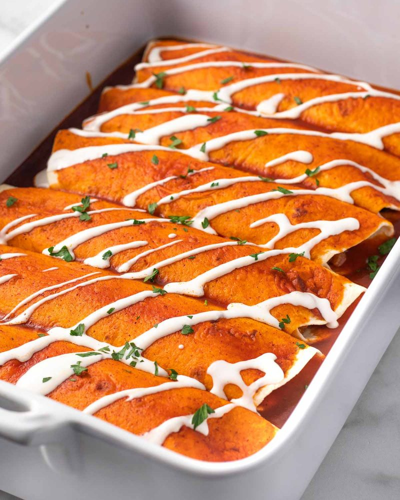 6 vegan enchiladas topped with red sauce, sour cream, and parsley in a baking dish.