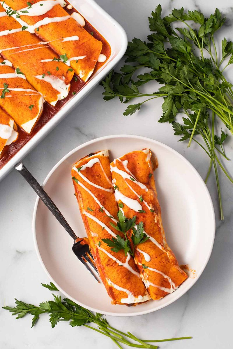 Two black bean enchiladas on a plate topped with a vegan sour cream drizzle with a fork. In the background is the pan of enchiladas and some parsley bundles.