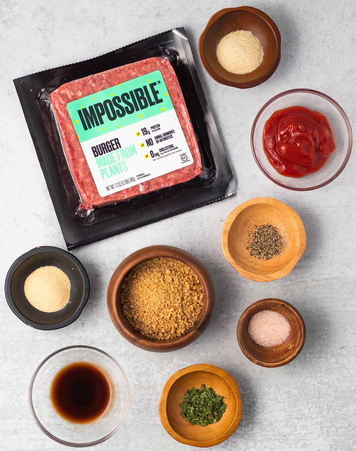 Ingredients for vegan meatloaf laid out on the table. A package of Impossible burger, and small bowls containing garlic powder, ketchup, pepper, salt, breadcrumbs, parsley, Worcestershire sauce, and onion powder.