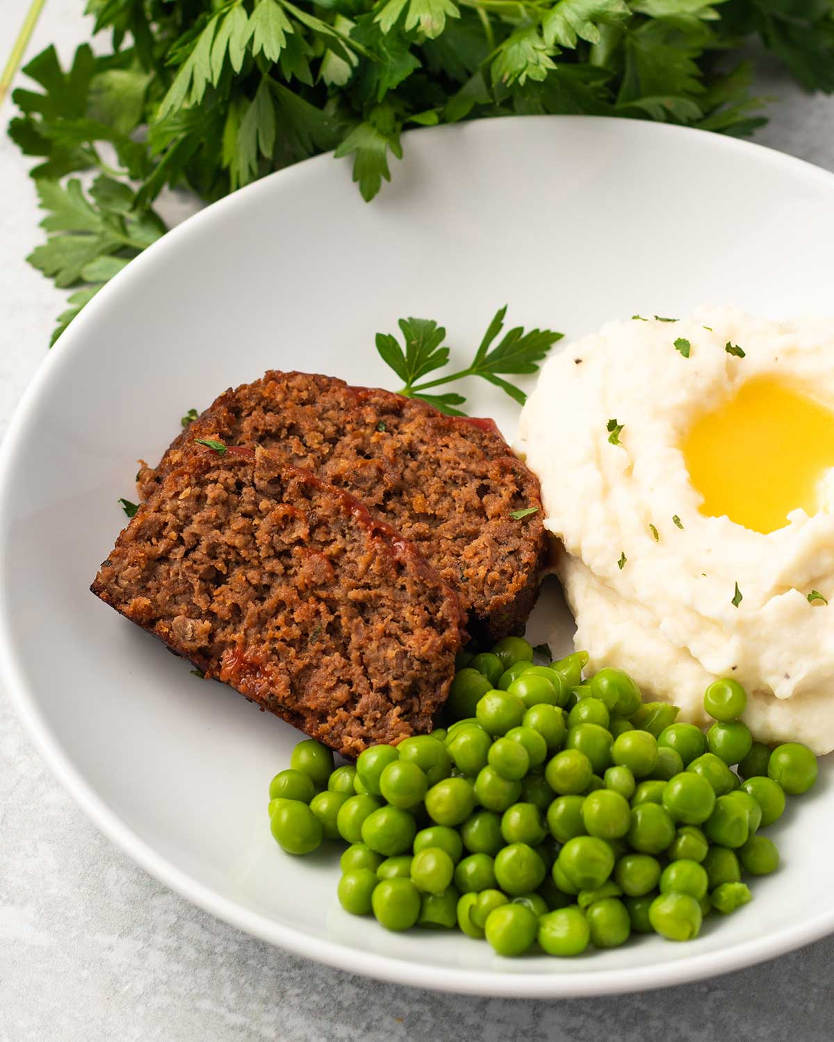 A round plate containing two slices of meatloaf, some mashed potatoes with vegan butter, and peas. There is parsley in the background and some sprinkled on the plate for garnish.