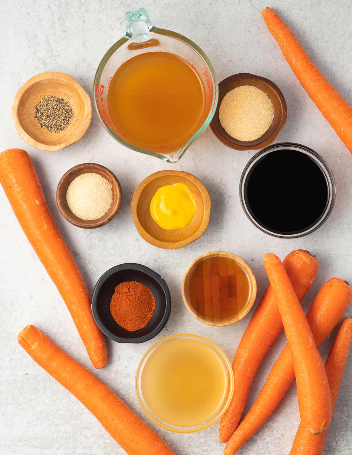 Ingredients for carrot dogs laid out on a surface. There are carrots scattered throughout, a measuring cup of vegetable broth, and small bowls containing black pepper, garlic powder, onion powder, mustard, soy sauce, smoked paprika, maple syrup, and apple cider vinegar.