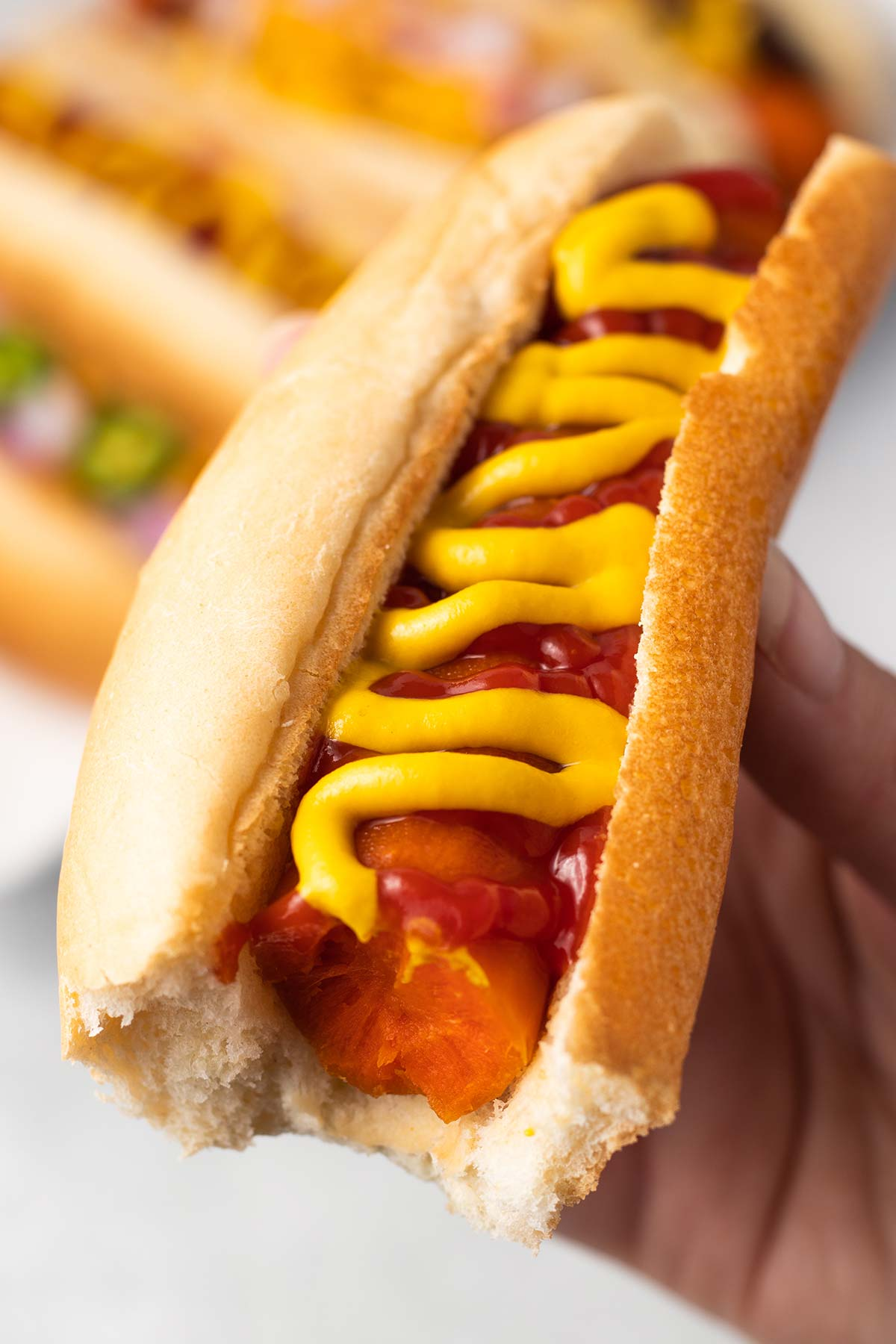 A hand holding up a carrot dog with a bite taken out. It's topped with a zig zag of ketchup and mustard.