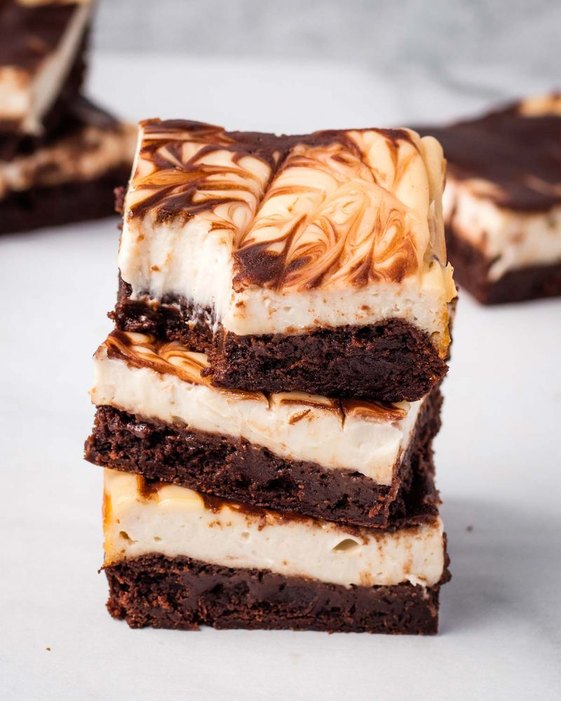 A stack of three squares of vegan cheesecake brownies. The top piece has a bite taken out of the corner. There are more slices in the bakground.
