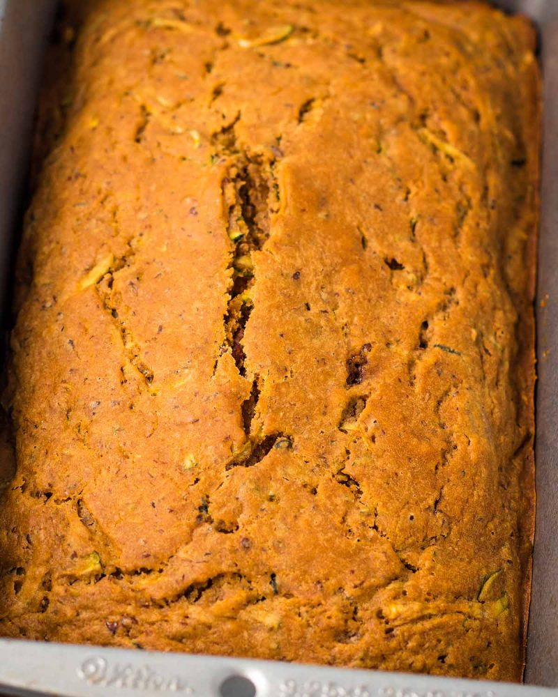 A close-up image of a baked loaf of zucchini bread in the pan.