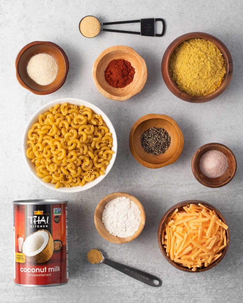 Ingredients on a surface in small bowls and measuring spoons: garlic powder, onion powder, paprika, nutritional yeast, pepper, salt, flour, vegan cheese, macaroni, dried mustard seed powder, and a can of coconut milk.